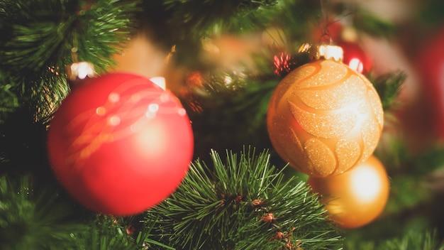 Close-up getinte foto van naalden en kleurrijke kerstballen op kerstboom. perfecte achtergrond voor wintervakanties en feesten
