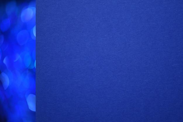 Close-up geweven blauw papier met kerst blauwe bokeh lijn aan de linkerkant.