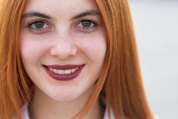 Close-up gezicht portret van een meisje met rood haar en heldere ogen.