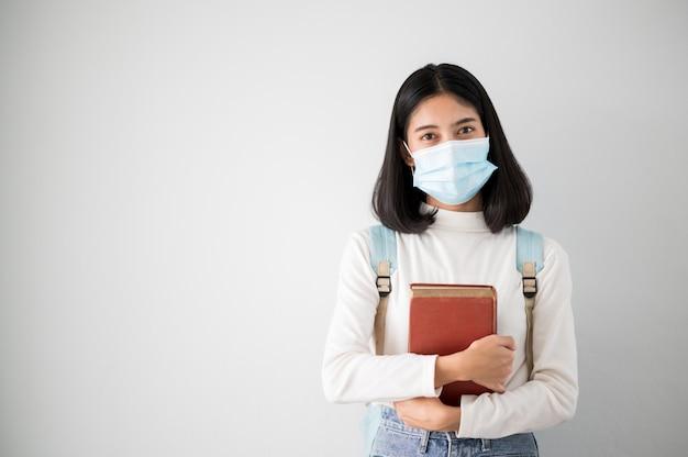 Close-up gezicht portret vrouwelijke aziatische universiteitsstudenten dragen een masker en houden sociale afstanden tijdens schooluren.