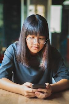 Close-up gezicht van aziatische tiener lachend gezicht met slimme telefoon in de hand