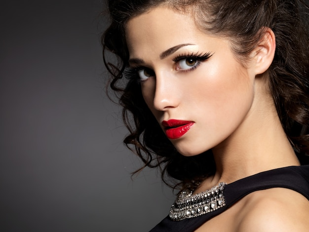 Close-up gezicht van brunette vrouw met mode make-up en rode lippen