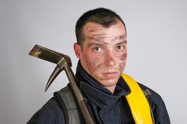 Close-up gezicht van dappere jongeman in uniform van brandweerman en koevoet gereedschap