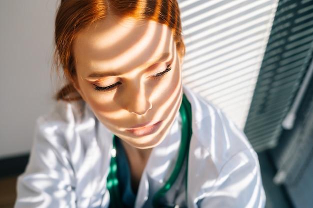 Close-up gezicht van depressieve trieste jonge vrouwelijke arts in witte jas zittend op de vloer knuffelen benen met handen in de buurt van raam.