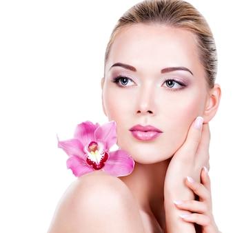 Close-up gezicht van een jonge mooie vrouw met een paarse oogmake-up en lippen. vrij volwassen meisje met bloem dichtbij het gezicht. - geïsoleerd op een witte achtergrond