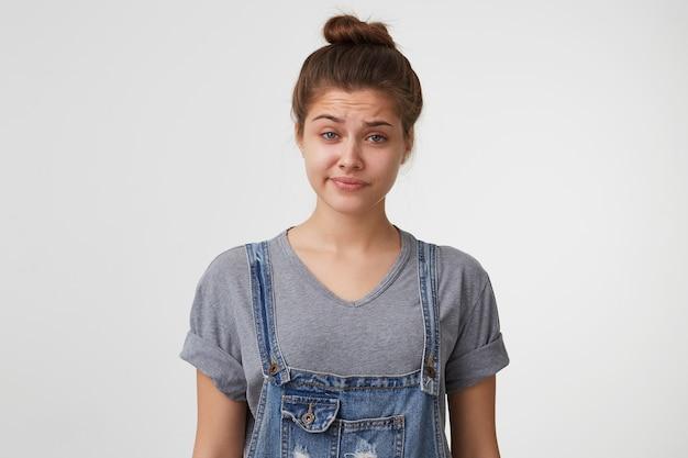 Close-up gezicht van een jonge vrouw met haar verzameld in een knot, draagt een denim overall, kijkt sceptisch van ongeloof Gratis Foto