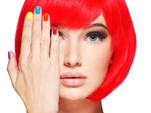 Close-up gezicht van een mooi meisje met heldere veelkleurige nagels.