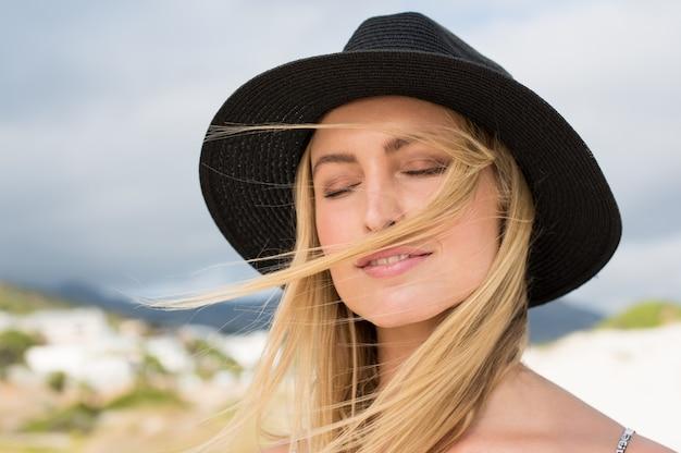Close-up gezicht van een mooie vrouw, gekleed in zwarte strohoed op een zonnige dag met haar ogen dicht