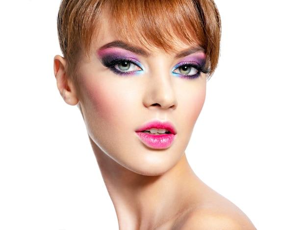 Close-up gezicht van een mooie vrouw met heldere, levendige make-up. mannequin met creatieve oogmake-up - die op wit wordt geïsoleerd. meisje met een gemberhaar. kort kapsel met pony
