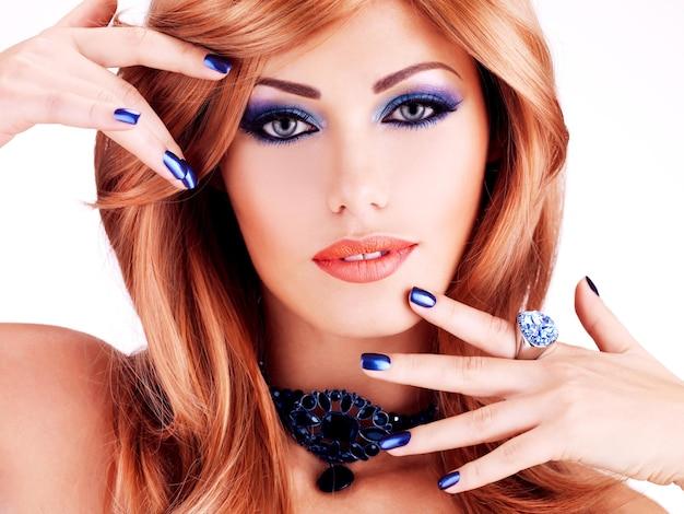 Close-up gezicht van een sensuele mooie vrouw met blauwe nagels, blauwe make-up en sexy rode lippen op witte muur