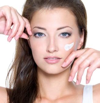 Close-up gezicht van een sexy vrouw met crème op gezicht geïsoleerd op wit