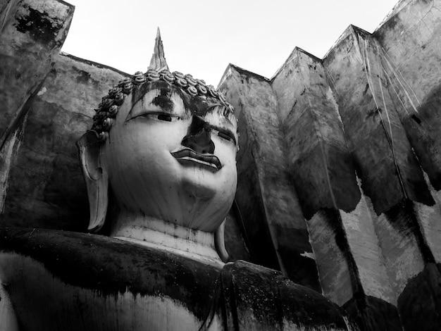 Close-up gezicht van het oude grote boeddhabeeld in de oude kerk in de wat sri chum-tempel, de beroemde bezienswaardigheid in het sukhothai historical park, een unesco-werelderfgoed in thailand, zwart-wit.