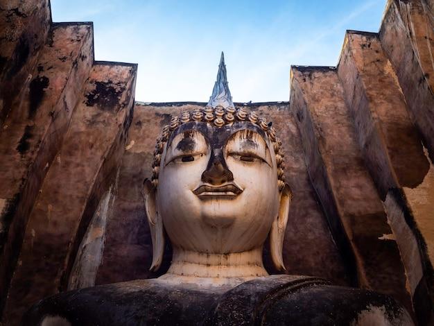 Close-up gezicht van het oude grote boeddhabeeld in de oude kerk in de wat sri chum-tempel, de beroemde bezienswaardigheid in het sukhothai historical park, een unesco-werelderfgoed in thailand.