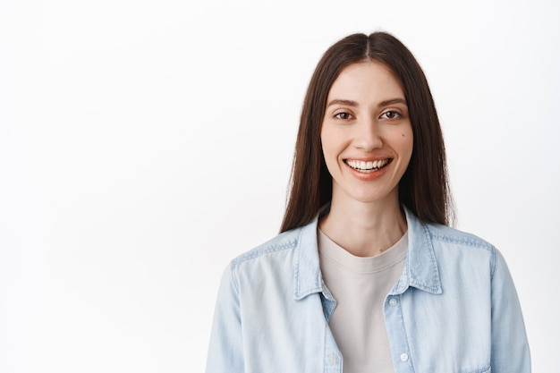 Close-up gezicht van jonge vrouw zonder make-up, naakte gezichtshuid en witte perfecte glimlach, gelukkig naar voren kijkend, staande in vrijetijdskleding