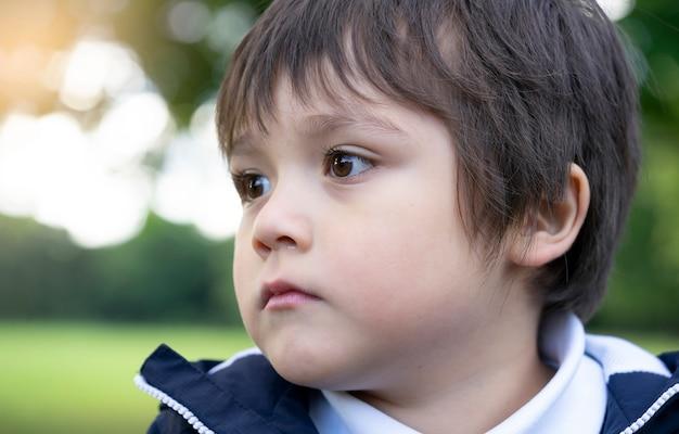 Close-up gezicht van kleine jongen met lopende neus, kind met allergie, tranende ogen en neus na het spelen in het park, kind heeft reflectie of hooikoorts van pullen in de lucht in de lente of zomer