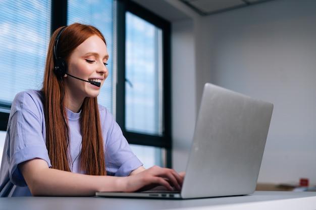 Close-up gezicht van lachende jonge vrouw operator met behulp van headset en laptopcomputer tijdens klantenondersteuning. callcenter operator in gesprek met klant met microfoon en koptelefoon.