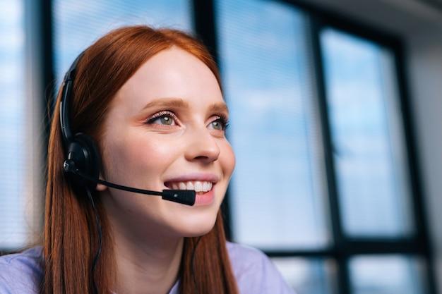 Close-up gezicht van mooie jonge vrouw operator met behulp van headset tijdens klantenondersteuning op kantoor aan huis.