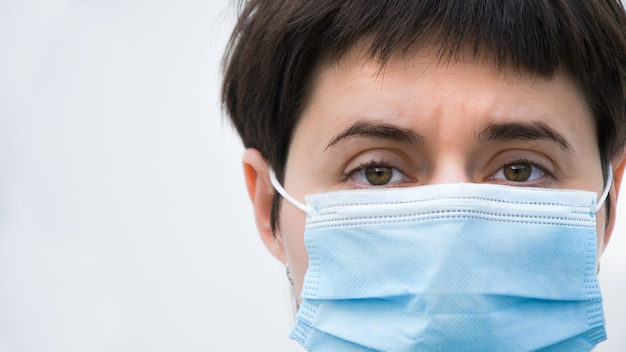 Close-up gezicht van vermoeide jonge brunette vrouw in medische wegwerp masker op witte achtergrond. vermoeide ogen van een dokter na een zware dienst. ruimte aan de linkerkant voor tekst.