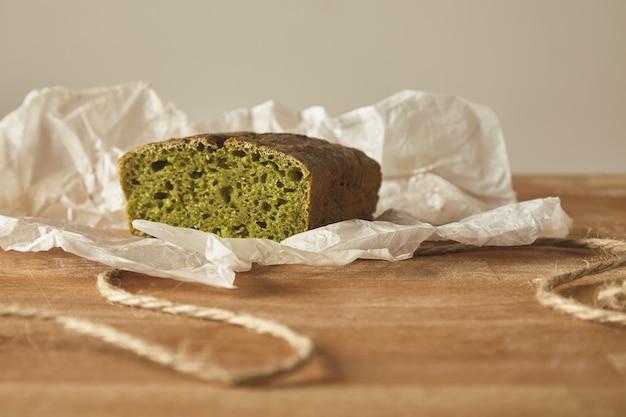 Close-up gezond dieet groen brood van spinash deeg op ambachtelijke papier geïsoleerd op een houten bord