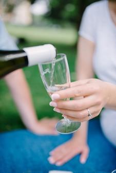 Close-up gieten champagne in glas op vrijgezellenfeest