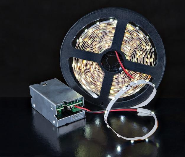 Close-up glanzende led-lichtstrip op spoel en spanningsadapter, op zwart.
