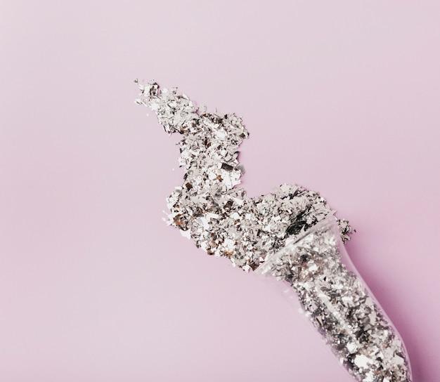 Close-up glas champagne gevuld met zilver glitter en kopie ruimte violette achtergrond