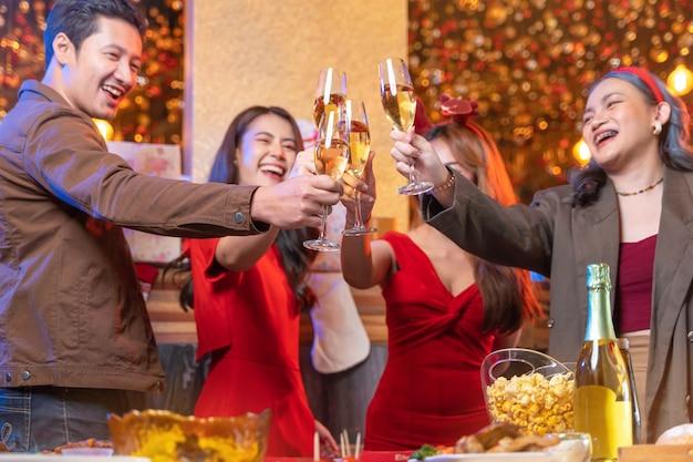 Close-up glazen rammelende glazen champagne met verlichting en glans partij van aziatische vriend