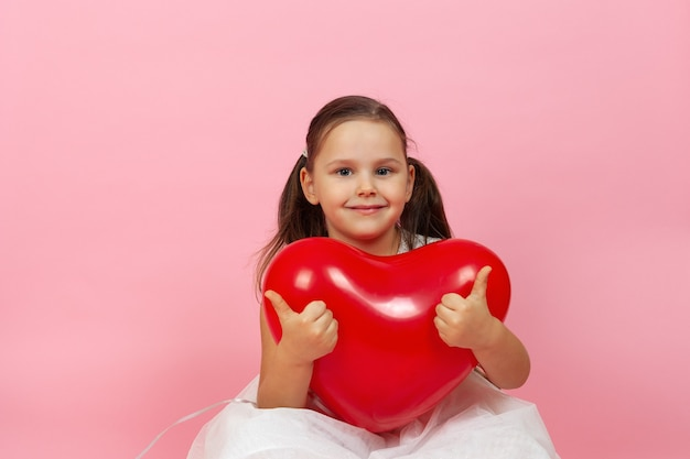 Close-up glimlachend kind in witte jurk met rode ballon in de vorm van hart, duimen opgevend