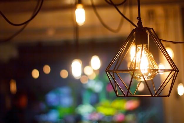 Close-up gloeiende hangende sferische retro uitstekende gloeiende bol van edison tegen achtergrond van vage andere lampen