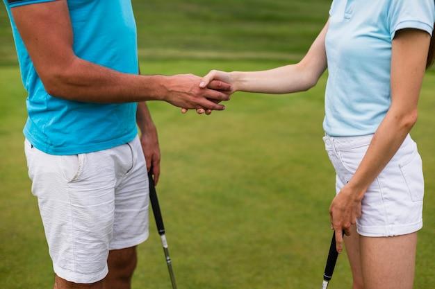 Close-up golfspelers handen schudden