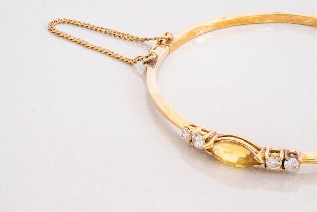 Close-up gouden armband met gele kiezelsteen op grijze marmeren steenachtergrond