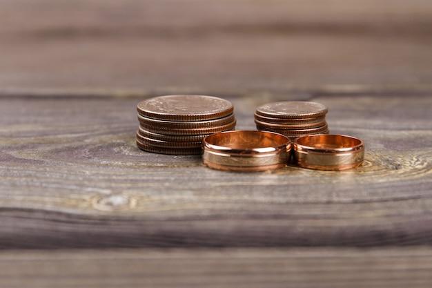 Close-up gouden munten en trouwringen. houten tafel achtergrond.