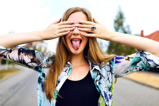 Close-up grappig portret van glimlachend blond meisje sluit haar ogen, koop haar handen, licht shirt, platteland, schoenen haar lange tong, heldere manicure.