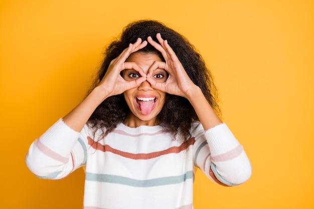 Close-up grappige gek rond vrolijk opgewonden plezier hipster jeugdmeisje maken verrekijker met haar vingers geïsoleerde heldere kleur muur