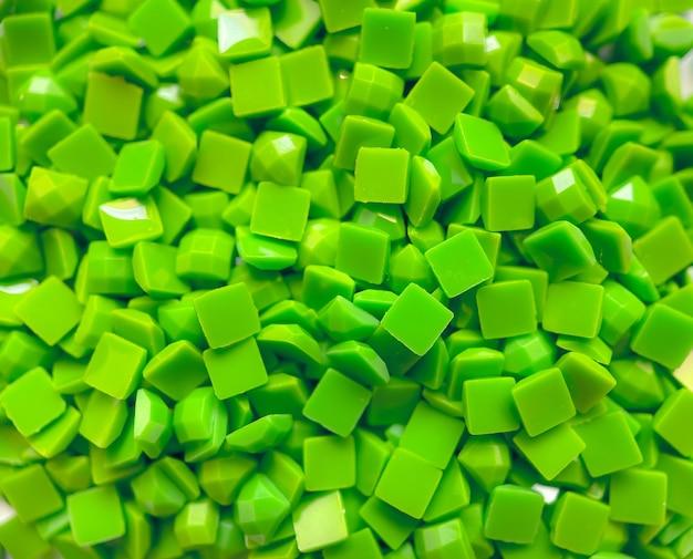 Close-up, groene vierkante diamanten voor diamant borduurwerk. hobby's en doe-het-zelf, materialen voor het maken van diamantborduurwerk.