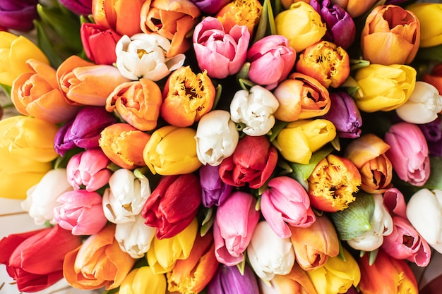 Close-up groot mooi boeket van gemengde tulpen. bloemachtergrond en behang. bloemen winkelconcept. mooi vers gesneden boeket. bloemen bezorgen