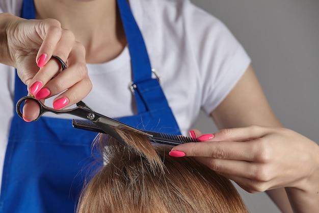 Close-up haar knippen. de handen van de kapper houden de uiteinden van het haar vast