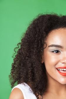 Close-up half gezicht portret van een mooie jonge afrikaanse vrouw make-up dragen, wegkijken geïsoleerd over groen