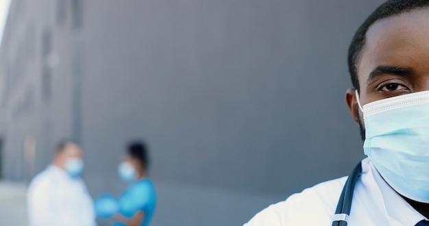 Close-up half gezicht van afrika amerikaanse man arts in medische masker camera kijken op grijze achtergrond met multi-etnische artsen. knappe mannelijke arts in ademhalingsbescherming. gezondheidszorg concept.
