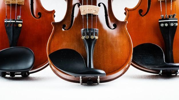 Close-up halve voorkant van drie violen gezet op achtergrond, tonen detail en een deel van de viool