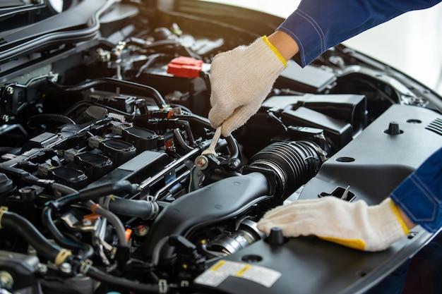 Close-up hand automonteur motor nieuwe auto in auto servicecentrum controleren.