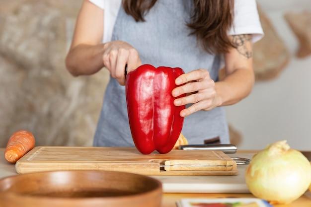 Close-up hand cuttin paprika