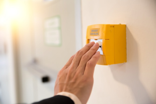 Close-up hand druk op noodschakelaar en verlaat de deur.