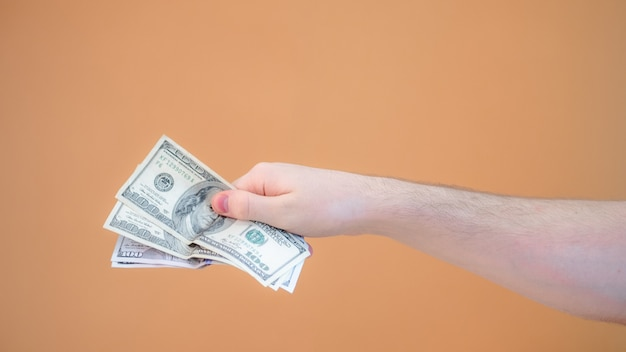 Close-up hand geeft een pak van vierhonderd dollar op oranje achtergrond