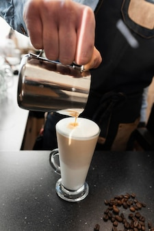 Close-up hand gieten melk in koffie