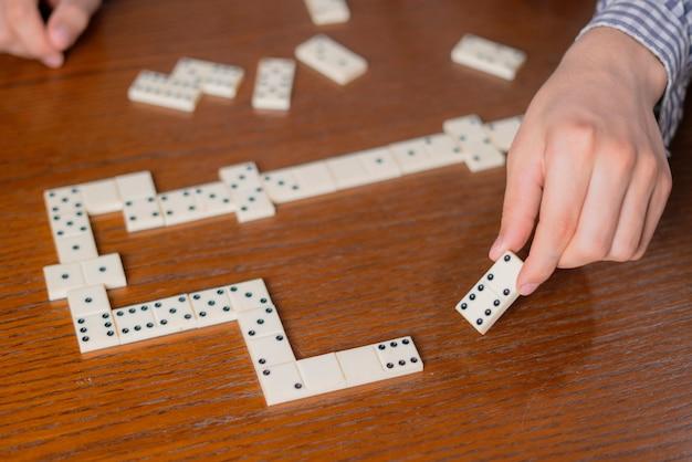Close-up hand houden domino stuk op houten tafel f