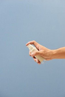 Close-up hand houden kleine spuitfles en sproeien