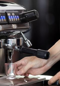 Close-up hand houden van het maken van koffie met machine in café. professionele moderne espressomachine giet warme drank in de beker. concept koffie in café.