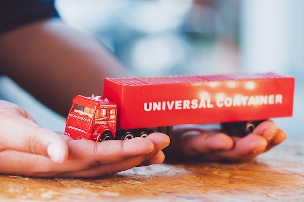 Close-up hand houdt de rode vrachtwagen universele container gebruiken voor logistiek en bedrijfsconcept
