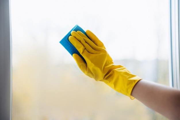 Close-up hand in beschermende gele handschoen met zwabber is het venster schoonmaken